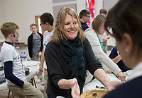 NWA Democrat-Gazette/CHARLIE KAIJO Volunteer Meg Kreuter hands off a pie during a Pi Day celebration, Thursday, March 13, 2019 at St. Vincent de Paul Catholic School in Rogers. <br /><br />Students at St. Vincent de Paul Catholic School celebrates Pi Day with a pie eating contest, games and a pi&Atilde;&plusmn;ata. Pi Day is an annual celebration of the mathematical constant &Iuml;&euro;. Pi Day is observed on March 14 since 3, 1, and 4 are the first three significant digits of &Iuml;&euro;.<br /><br />&quot;[We're] giving the kids an opportunity to get out of the classroom, do something fun and incorporate math,&quot; said Amy Liddell, seventh and eighth grade math teacher.