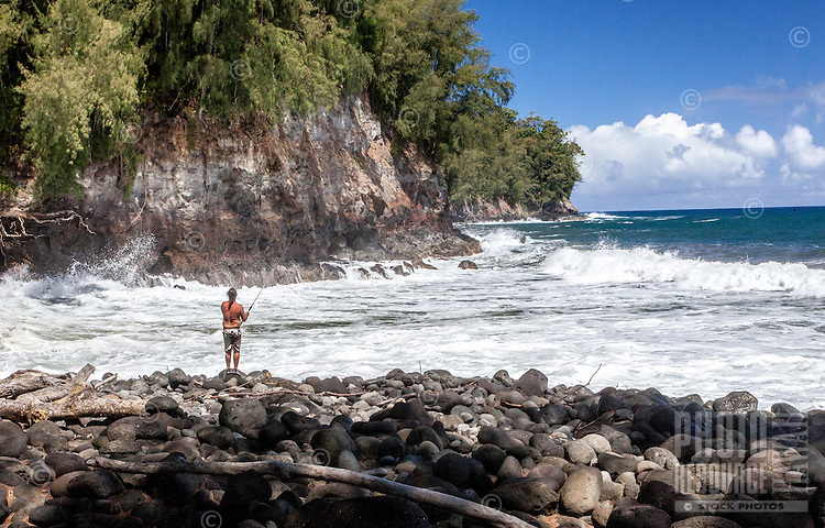 Caucasian man fishing from rocky shoreline at Kolekole Beach Park in Honomu, Big Island.