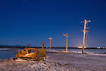 A rusting hulk of a car and decaying power poles stand in the salt encrusted mud flats on the shores of the Salton Sea near Niland, california
