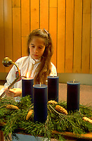 Youth age 12 lighting Advent candles in church. St Paul Minnesota USA