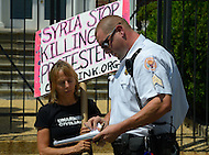 August 12, 2011 (Washington, DC)  Code Pink cofounder Madea Benjamin is served with a trespass notice by a member of the Uniformed Secret Service after protesting on the steps of the Syrian Embassy in Washington. Members of the group Code Pink protested what they consider Syria's human rights violations against its own people.  (Photo: Media Images International)