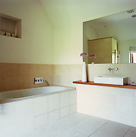 The minimal bathroom has a tiled floor and half-tiled walls
