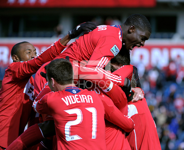 Chicago Fire defender Jalil Anibaba (6, top of pile) celebrates Diego Chaves' penalty kick goal.  The Chicago Fire defeated Sporting KC 3-2 at Toyota Park in Bridgeview, IL on March 27, 2011.