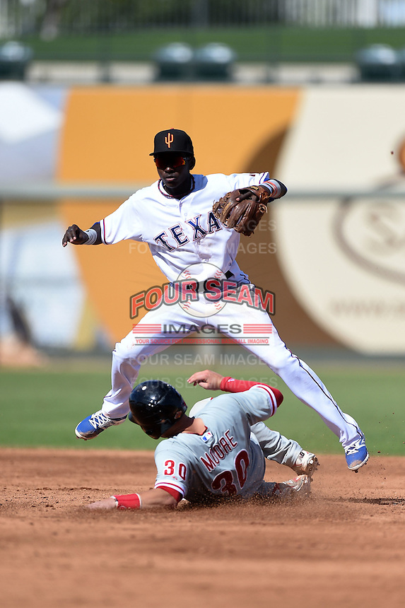 Surprise Saguaros infielder Michael De Leon (55) turns a double play as Logan Moore (30) skies in during an Arizona Fall League game against the Scottsdale Scorpions on October 16, 2014 at Surprise Stadium in Surprise, Arizona.  Surprise defeated Scottsdale 7-3.  (Mike Janes/Four Seam Images)