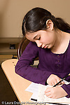 Elementary school Grade 5 arts enrichment female student working on assignment vertical