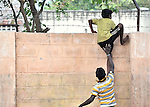 Children who work as scavengers in the municipal dump in Chennai, India, are hosted in a night shelter by MCCSS. Here one climbs a wall, with help, to retrieve a lost cricket ball.