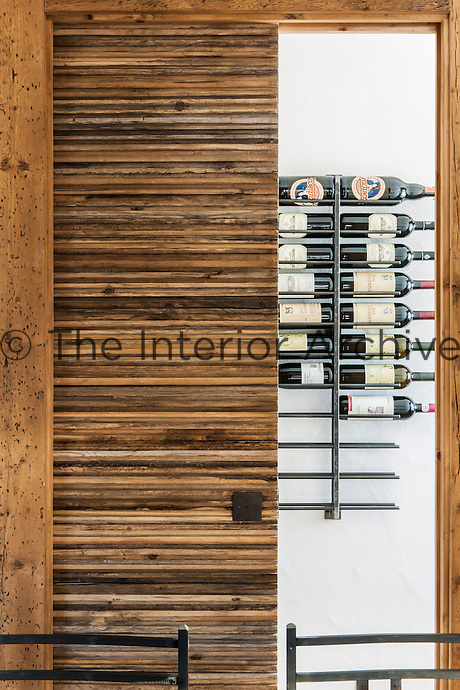 Wine bottles are stored in a contemporary rack in the kitchen behind a wood-clad sliding door