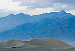 Grapevine Mountains loom over the Mesquite Sand Dunes as the wind blows the sand during an approaching spring storm in Death Valley National park.