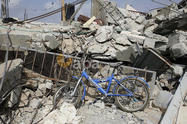 A bicycle is seen on the rubble of a house, that witnesses said was damaged during a seven-week Israeli offensive, in Khuzaa, east of Khan Younis, in the southern Gaza Strip, in Oct. 19, 2014. Khuzaa is threatened with an environmental and humanitarian disaster due to the Israeli offensive on Gaza strip. An open-ended ceasefire between Israel and Hamas-led Gaza militants, mediated by Egypt, took effect on August 26 after a seven-week conflict. It called for an indefinite halt to hostilities, the immediate opening of Gaza's blockaded crossings with Israel and Egypt, and a widening of the territory's fishing zone in the Mediterranean. Photo by Abed Rahim Khatib