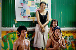 """Thach """"Homie"""" Chanreangsey, 20, peer mentor and dance teacher, holding Srey Nich, 2, at right,  Makara """"Slick"""" Sorn, 19, dance student, left, and Set Yav, cleaner at the center, and Srey Nich's mom, watch a breakdancing class at Tiny Toones hip hop youth center, in Phnom Penh, Cambodia, on Thursday, April 22, 2010. The center also provides shelter for at-risk youth.."""