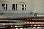 Man walking a bicycle along the platform of a train station between Beijing and Datong, China.