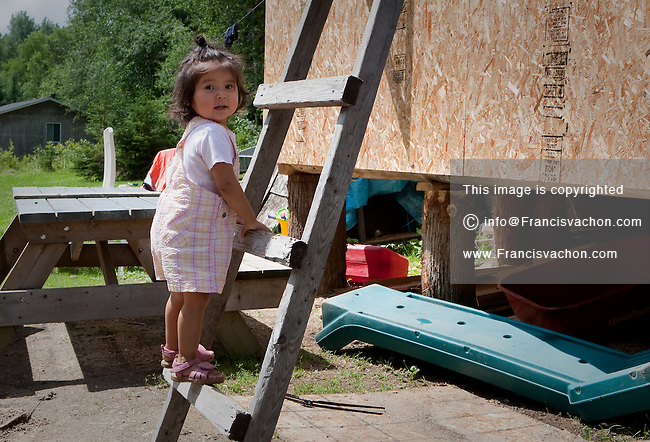 20 months old Janice Papatie climbs a ladder on her house in the algonquin Anicinape community of Kitcisakik in Quebec, Canada, July 18, 2009. The aboriginals living in Kitcisakik, a small algonquin Anicinape community, don't have an official statue and are considered squatters by the crown. They don't have access to electricity and running water in their houses that are very modest.