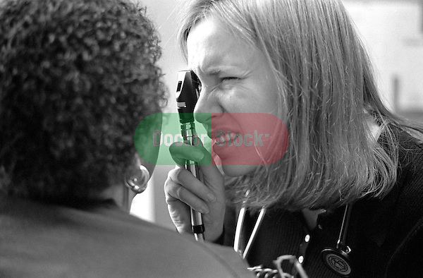 Young female internal medicine resident physician examining eye of African-American female
