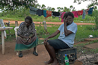 Aboriginal  women sit smoking cigarettes and resting after hanging clothes and doing laundry for their families.