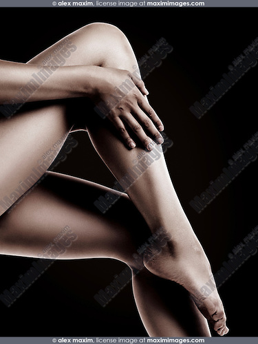 Closeup of bare woman legs with smooth skin isolated on black background