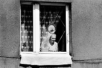 Poland. Silesia. Ruda Slaska. Corpus Christi day. Corpus Christi Day is the Thursday after Trinity Sunday, or about seven weeks after Easter. Christian holy day - a religious holiday for Christians. Woman at the window. Picture of the Pope John Paul II, originaly from Poland and leader of the catholic religion. Ruda Slaska is a small town, distant 20 km from Katowice.© 1991 Didier Ruef