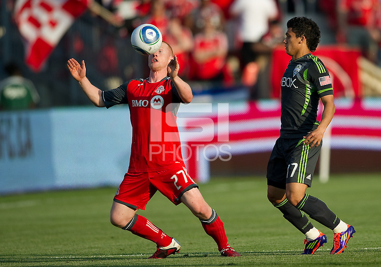 Toronto FC defender  Richard Eckersley #27 and Seattle Sounders FC forward Fredy Montero #17 in action during an MLS game between the Seattle Sounders FC and the Toronto FC at BMO Field in Toronto on June 18, 2011..The Seattle Sounders FC won 1-0.