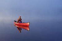 canoeing, canoe, Vermont, VT, Woman paddling a red canoe on Mollys Falls Pond at sunrise in the fog.