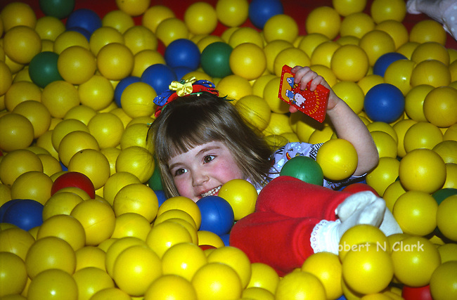 Young girl playing in ball pit with colorful air balls and big smile on her face