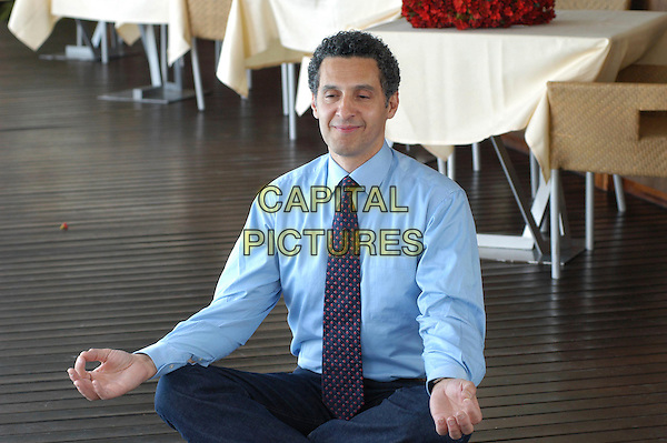 """JOHN TURTURRO.Photocall for """"Romance & Cigarettes"""" at Hotel Exedra, Rome, Italy..May 3rd, 2006.Ref: CAV.full length blue shirt tie sitting legs crossed meditating funny .www.capitalpictures.com.sales@capitalpictures.com.© Capital Pictures."""