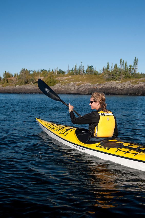 A female sea kayaker paddles the rugged shoreline of Lake Superior at Isle Royale National Park.