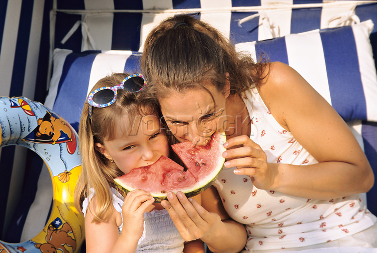 Mother and daughter eating water melon