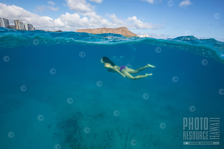 Young woman swimming off the shores of Waikiki, with Diamond Head in the background