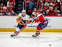 WASHINGTON, DC - JANUARY 31: Mathew Barzal #13 of the New York Islanders sends a pass away from Carl Hagelin #62 of the Washington Capitals during a game between New York Islanders and Washington Capitals at Capital One Arena on January 31, 2020 in Washington, DC.