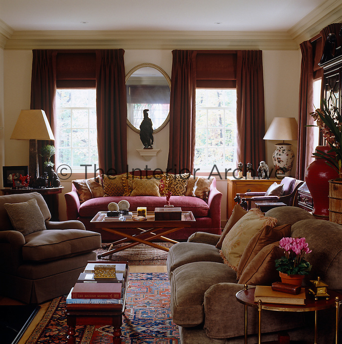 A 19th-century French oval mirror and a Buccellati silver monkey on walls bathed in a custom sand color with red curtains and red chenille sofa to warm up the natural palette