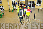 CHECKING OUT: Fire service.personnel at the Earl.of Desmond Hotel wade.through the water outside.Tralee on Wednesday.morning.