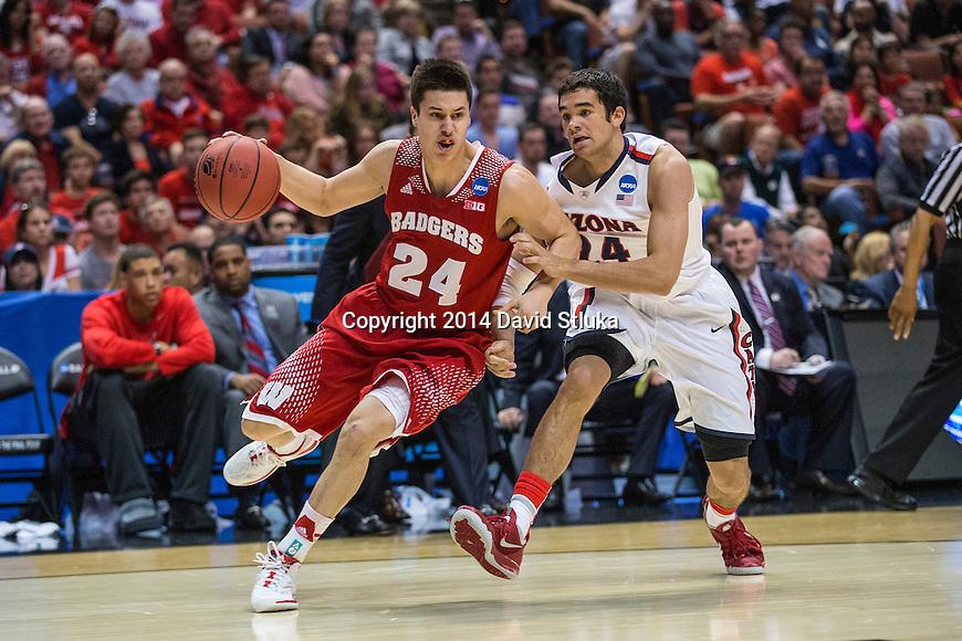 Wisconsin Badgers guard Bronson Koenig (24) drives around Arizona Wildcats guard Elliott Pitts (24) during the Western Regional Final NCAA college basketball tournament game Saturday, March 29, 2014 in Anaheim, California. The Badgers won 64-63 (OT). (Photo by David Stluka)
