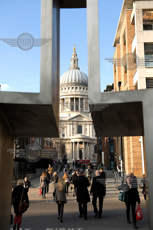 St Paul's Cathedral seen through sculptures at the junction of Peters Hill and Queen Victoria Street in the City of London.