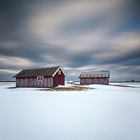 Two red farm sheds below stormy winter sky, Austvågøy, Lofoten Islands, Norway
