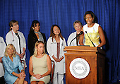 United States First Lady Michelle Obama talks at an event about the Affordable Care Act at George Washington University Hospital, with, Dr. Jill Biden, sitting, from left, and Maggie Roberts, on Wednesday, July 14, 2010, in Washington, DC.  Roberts gave a personal story about her son's medical needs. .Credit: Leslie E. Kossoff - Pool via CNP