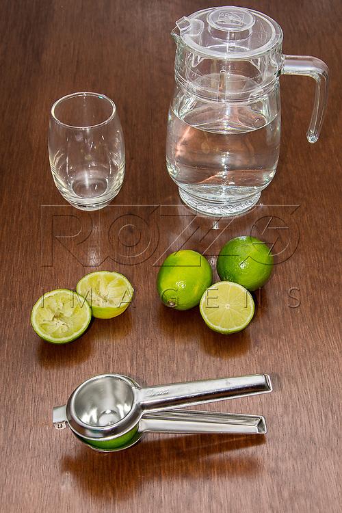 Preparando uma limonada com espremedor, limões inteiros e espremidos, uma jarra de água e um copo vazio, São Paulo - SP, 10/2016.
