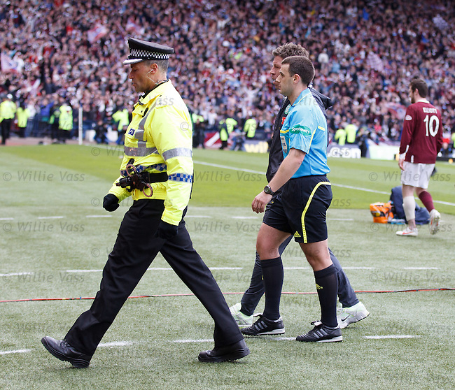 Referee Euan Norris escorted off the pitch by the match commander