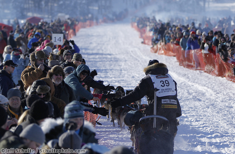 Sunday, March 4, 2012  Ken Anderson high fives spectators in the starting chute at the restart of Iditarod 2012 in Willow, Alaska.
