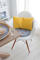 A homemade cushion with playful orange buttons covers the seat of a retro Charles and Ray Eames chair in the dining area