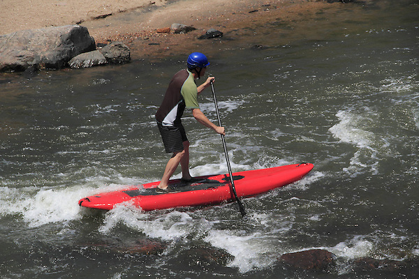 Standup paddleboarder in whitewater, Denver, Colorado, USA.
