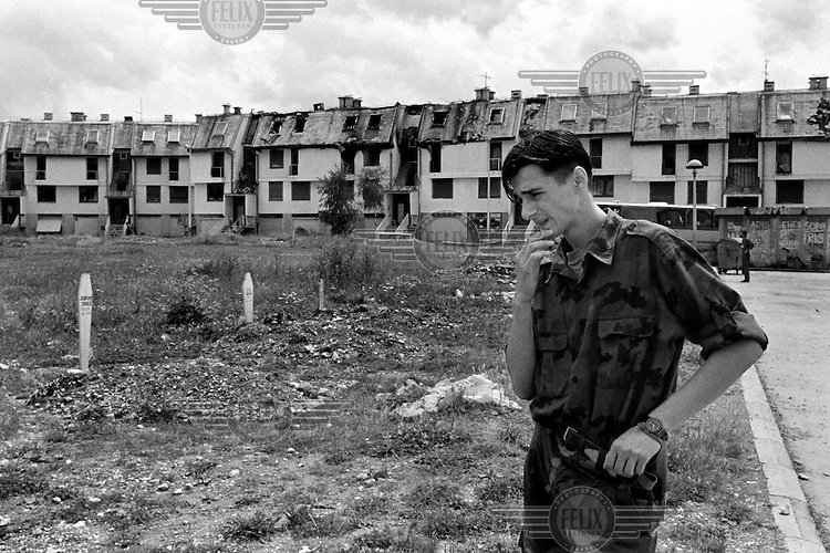 A young Bosnian government fighter pauses at a makeshift graveyard in Sarajevo on June 30, 1992. Several of his comrades are buried here.