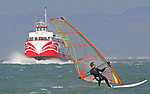 Wind surfing under the Golden Gate Bridge passing the Red and White Ferry on San Francisco Bay.