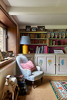 The sitting room is a glorious mismatch of colour, pattern and texture. In one corner an inherited chair has been re-upholstered in a Molly Mahon fabric. Hand-painted motifs decorate the built-in cupboards.