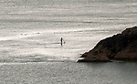 Langland Bay, Swansea, UK, 1st April 2020.<br />A lone stand up paddleboarder makes her way past Snaple Point at Langland Bay near Swansea today in the sunny weather.