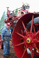 Antique Steam Traction Engine, Saanichton, BC, British Columbia, Canada - a Volunteer Engineer stands beside a Historic Steam Powered Agricultural Machine at the Saanich Historical Artifacts Society