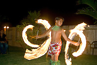 Young fire knife dancer spins his knives at a party in Laie.