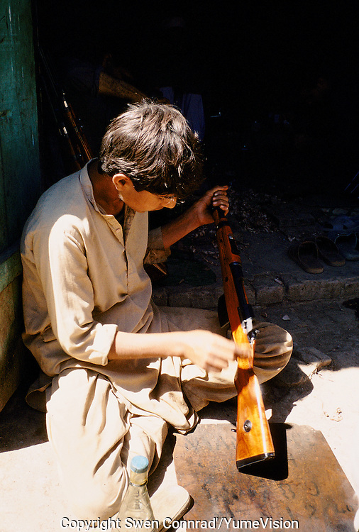 A young boy painting Butt's for new made rifles. Darra town in Pakistan clandestinely provides arms to more than eight Central Asian countries.