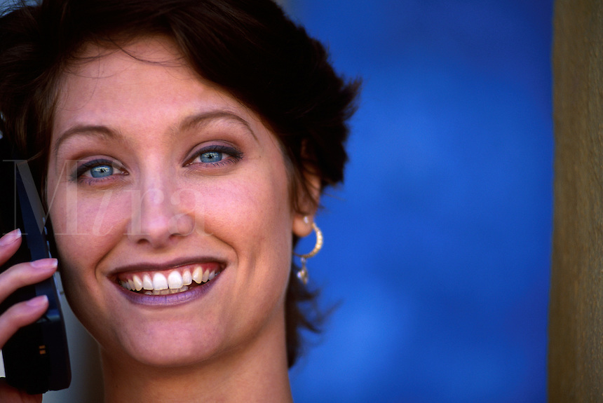 Portrait of a smiling female model with blue-green eyes as she talks on a cell phone.