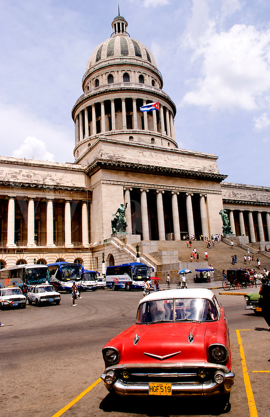 Havana capitol city of Cuba with old classic 50s autos going by the capitol building street