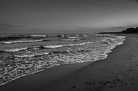 Havsvågor mot sandstrand i skymning över havet på Österlen Skåne i svartvitt