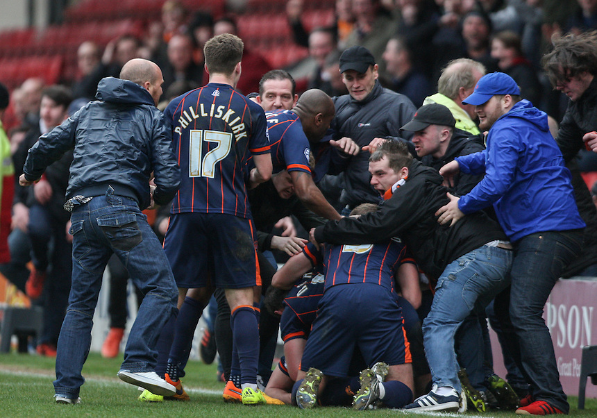Blackpool fans mob the players after Tom Aldred scored the winning goal<br /> <br /> Photographer Alex Dodd/CameraSport<br /> <br /> Football - The Football League Sky Bet League One - Crewe Alexandra v Blackpool - Saturday 19th March 2016 - Alexandra Stadium - Crewe    <br /> <br /> &copy; CameraSport - 43 Linden Ave. Countesthorpe. Leicester. England. LE8 5PG - Tel: +44 (0) 116 277 4147 - admin@camerasport.com - www.camerasport.com